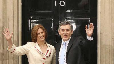 英国新首相布朗和夫人萨拉在唐宁街10号首相官邸前向支持者挥手。