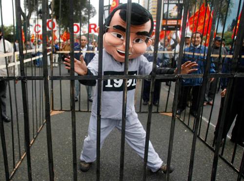 """6月27日,秘鲁首都利马街头,抗议者们将假扮成秘鲁前总统藤森的同伴关进笼子里""""围殴"""",以泄心头之恨。"""