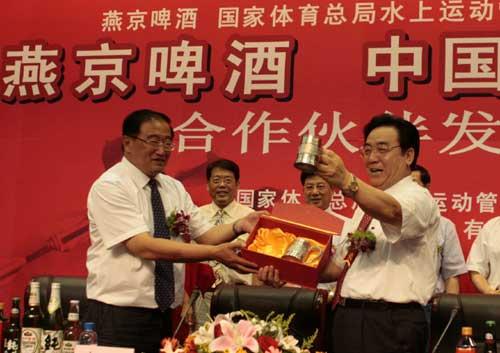 李福成(右)向中国皮划艇队赠送纪念金杯