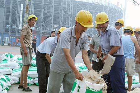 图文:奥运沙排比赛用沙抵京 工人将沙子装袋