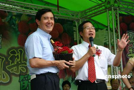 """六月三十日,中国国民党大选候选人马英九(左),在台北市一家农产品市场为南投县拍卖一瓶被称""""马英酒""""的荔枝王酒,结果拍出十六万九千九百九十九元新台币的高价。拍卖所得捐赠给南投的一家慈善机构。台湾南投县有四棵树龄三百多年的荔枝树,用其果酿制的""""荔枝王酒""""非常名贵。 中新社发 耿军 摄"""