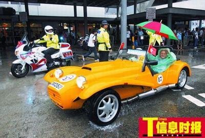 驾驶敞篷老爷车的车主打着雨伞参加老爷车巡游。萧嘉宁 摄