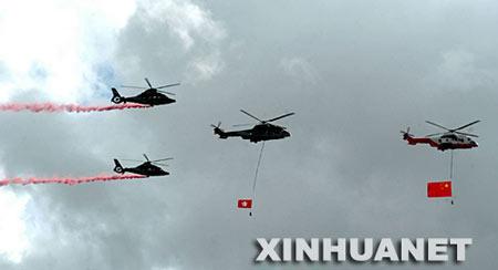 7月1日,香港金紫荆广场举行升旗仪式,庆祝香港回归祖国十周年。这是直升机携带国旗和区旗飞过维多利亚港上空。 新华社记者  卢炳辉摄