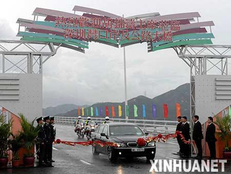 7月1日,深圳湾口岸开通仪式举行。这是国家主席胡锦涛乘坐的专车冲过深圳湾公路大桥彩带。 新华社记者 吕小炜摄