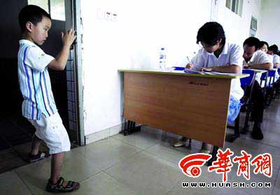 8岁的张睿杰给参加考试的妈妈寇苗苗拍照留念