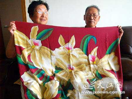 班主任华柏春(右)和夫人林久如向记者展示陈竺送给他们的真丝方巾