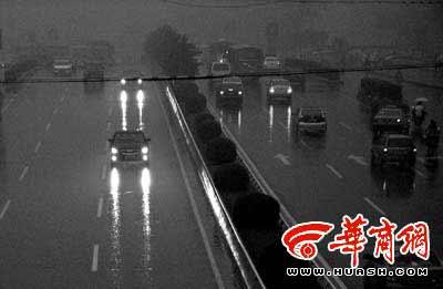 持续阴雨使能见度降低,才下午五点半,西安市长安路上行驶的车辆已经打开车灯 本报记者张杰摄
