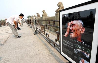 """2007年7月7日,""""卢沟桥事变""""和中国人民抗日战争全面爆发70周年纪念日,摄影作品""""历史的见证""""在卢沟桥石狮子下方展出,这些石狮子和战争受害者曾经见证了当年的激战场面。 吴长青/摄"""