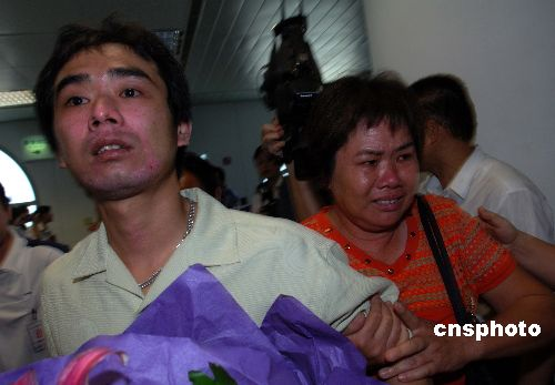 家住厦门市海沧区的厦门籍船员林景德抵达机场时,前来迎接的母亲紧紧握住儿子热泪盈眶。