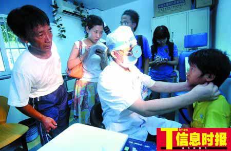 张慧敏在眼耳口鼻科检查时,爸爸在旁边看着,露出焦虑的神情。