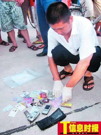 当地警方向记者展示熊孙铭的遗物:手机、数码相机、他和妻子的身份证、现金、钥匙等。