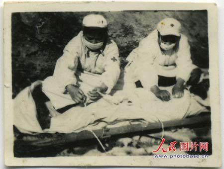 护士官义芝(左)和何成君在为黄继光遗体裹白布