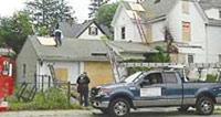 麻州布莱恩树镇的消防员摆乌龙,弄错演习地点,破坏了一栋民宅的屋顶、墙壁、窗户。图为有关人员事后忙着用木板遮住破洞。(美国《世界日报》图)