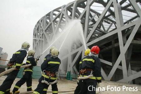 """图文:""""鸟巢""""举行联合消防演习 消防员在灭火"""