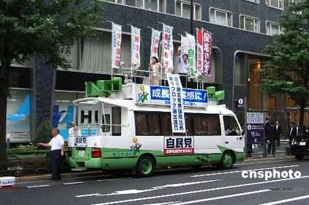 图为新任防卫相小池百合子在东京四谷车站前为自民党候选人佐藤正久拉选票。 中新社发 侯宇 摄