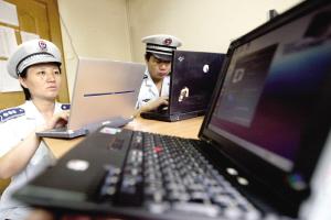 城管队员检查骗子的二手电脑。本报记者 王俭 摄