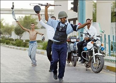 一名伊拉克警察在巴格达与民众庆祝伊拉克足球胜利