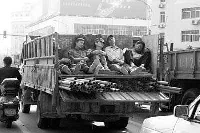 一群农民工在装满钢筋的车上打着盹,他们在为这个城市做着贡献的时候却依然被城市拒绝。