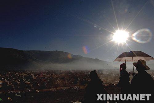"""7月25日,一对藏族夫妇带着孩子在观赏早晨的""""帐篷城""""。"""