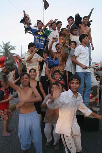 图文:伊拉克球迷狂欢死伤57人 球迷爬上警车