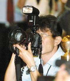 """拍""""总统""""不是容易的事,""""总统府""""摄影官简志宏手上的相机可不轻。(图片来源:台湾联合新闻网)"""