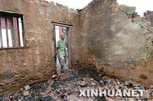 7月29日,湖北恩施市高桥坝村的高显声老人在查看自家垮塌的房屋。