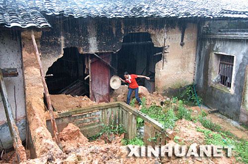 7月29日,湖北恩施市高桥坝村村民陈孝碧在查看严重受损的房屋。