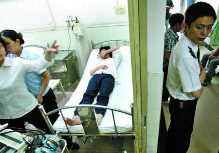 几名员工在医院接受治疗,他们所在的物业公司派出4名保安在医院病房门口看守,不准记者采访。朱元斌 摄