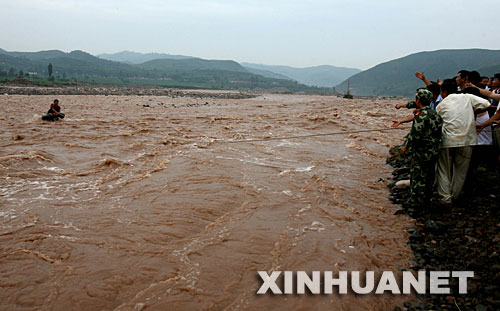 7月30日,救援人员营救两名被困河中的村民。