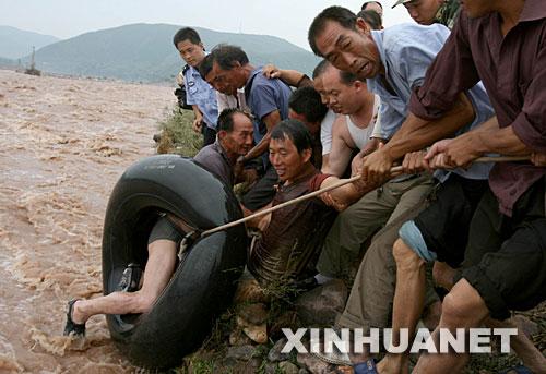 7月30日,救援人员将两名被困村民从河中救起。