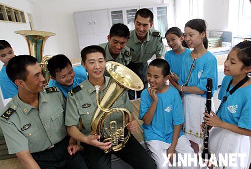 8月1日,小演员向三军仪仗队的战士介绍吹奏管乐的方法。当日,北京市海淀区五一小学金帆管乐团的近60名小学生来到中国人民解放军陆海空三军仪仗队驻地,参观军营,并为官兵们演出。 新华社发(陈晓根 摄)