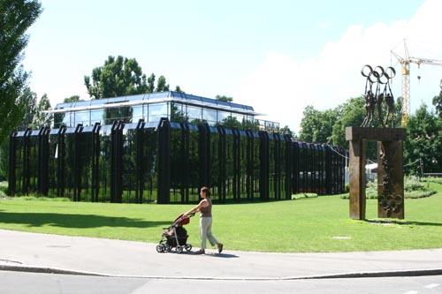 国际奥委会总部大楼外景,一名妇女推着婴儿车悠然走过楼前的通道。