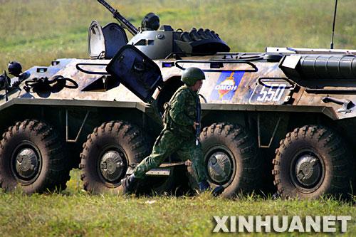 8月5日,一名俄军特战队员从装甲车前跑过。新华社记者 李刚摄