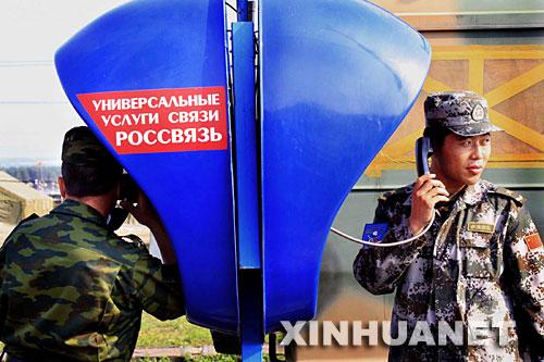 8月4日,在俄罗斯的车里雅宾斯克,中俄军人用野营村内的磁卡电话与外界沟通。新华社记者李刚摄