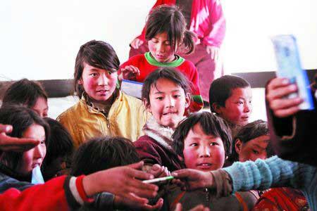 老师正在给多多学童们派发铅笔,一名小女孩静静地站在后排等待着老师派给自己,眼睛里满满的都是期待。
