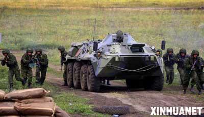 """8月6日,在俄罗斯车里雅宾斯克举行的实兵合练中,参演部队在装甲车掩护下向""""恐怖分子""""发起攻击。参加""""和平使命-2007""""上海合作组织成员国武装力量联合反恐军事演习的各国部队当日下午在车里雅宾斯克举行了首次实兵合练。 新华社记者李刚摄"""