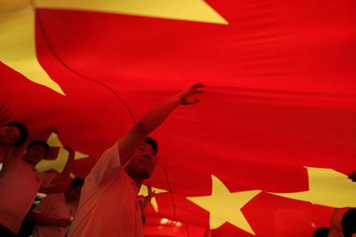 图文:上海庆祝倒计时一周年 众人顶起巨大国旗