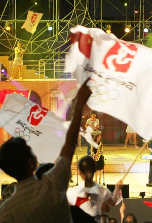 上海市民在晚会上摇旗庆祝北京奥运会倒计时一周年的来临