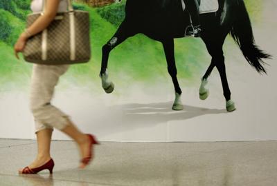 图文:香港庆祝倒计时一周年 一女士走过海报