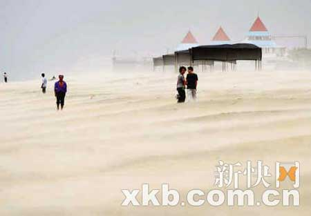 强风吹袭沙滩,厦门海边昨日恍如遭遇沙尘暴。