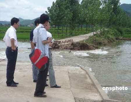 资料图为湖北省京山县坪坝镇通往丁畈村的道路被冲毁,过往民众只能望水兴叹。 中新社发 徐金波 摄