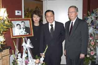 赵小兰(左)和父亲赵锡成(中)、丈夫麦康纳尔在父母早年的结婚照前合影。(美国《侨报》/管黎明 摄)