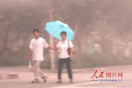 8月13日一大早,一位妇女走在吐鲁番街头打着伞遮挡严重的浮尘。