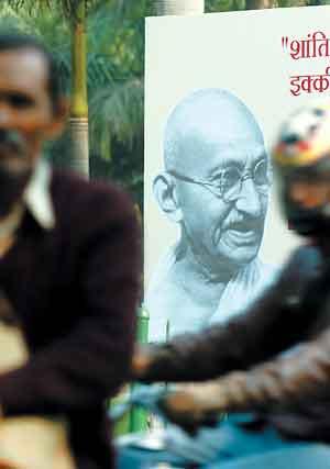 新德里市民骑车经过街头的圣雄甘地像