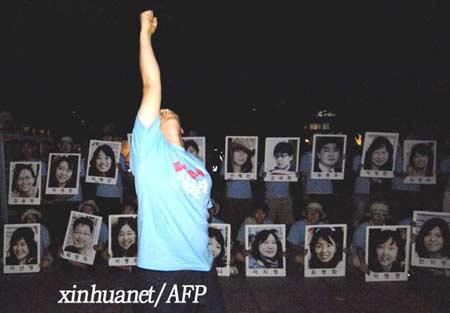 8月3日,一些韩国民众手持韩国人质照片在美国驻韩使馆前举行集会,要求美方帮助营救在阿富汗遭绑架的21名韩国人质。 新华社/法新