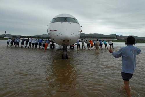 2007年8月12日上午,在烟台国际机场,山东航空公司烟台分公司的工作人员正推着一架小型飞机走出深水。