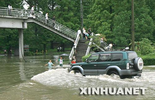 8月14日,在朝鲜首都平壤,一辆汽车驶过被水淹没的街道。