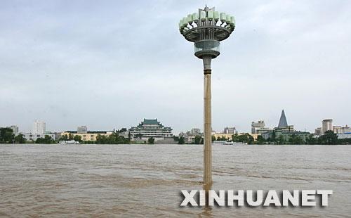 8月14日,朝鲜首都平壤市内大同江岸边人行道上的灯柱浸泡在上涨的江水中。