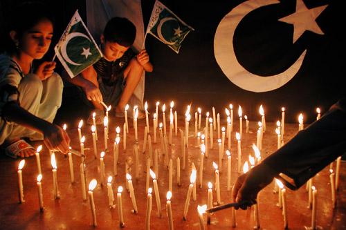 8月14日,巴基斯坦白沙瓦,孩子们点燃蜡烛庆祝独立60周年。