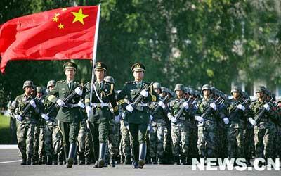 """中国士兵与国旗。8月11日日上午,""""和平使命-207""""联合反恐军事演习第二阶段誓师动员大会在在俄军第34摩托化步兵师295团阅兵场举行。哈、中、吉、俄、塔、乌六国4000余名官兵组成30个方阵,在阅兵场上庄严列阵。 新华网 李宣良 摄"""
